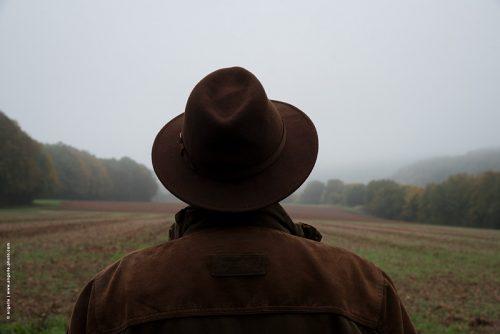 photo © angelle homme nature champ culture regarder de dos chapeau espace brouillard
